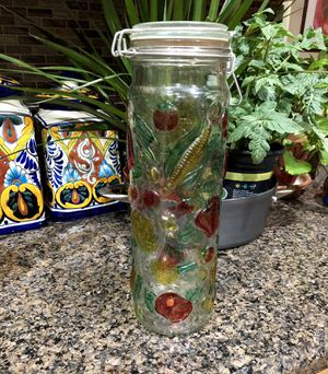 Pretty tall glass storage container with metal clasp. Cute fruit design. Container is 13 inches tall. for Sale in Tolleson, AZ