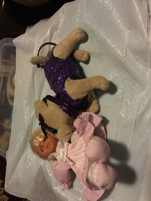 A beautiful doll with a lovely purse dog color purple it have a zipper on the purse for Sale in North Las Vegas, NV