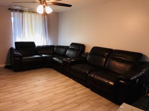Brown leather sectional armchair for 6 to 8 people in excellent conditions with 2 side recliners and cup holder table added 2 usb confections Adjusta for Sale in Phoenix, AZ