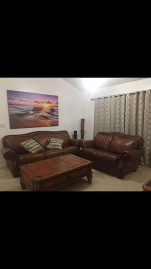 Two brown leather couches in good condition with large matching coffee table and two decorative items for Sale in Miramar, FL