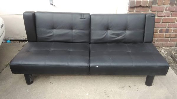 Black leather futon with cup holders on the armrest.