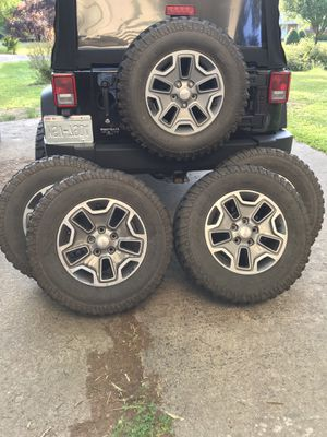 Jeep Wrangler tires and wheels 255/75R17 spare tire is brand new . The other 4 tires have about 60 % tread on them . for Sale in Durham, NC