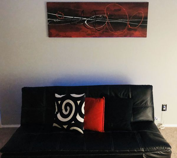 Convertible Futon Sofa Bed in black leather, Canvas wall picture, and decorative pillow covers!