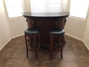 Bar with matching swivel top stools. Granite top and plenty of storage. for Sale in Gilbert, AZ