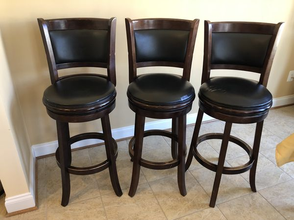 Three brown wooden frame black leather padded bar stools