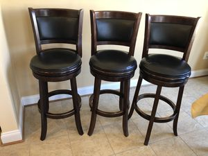 Three brown wooden frame black leather padded bar stools for Sale in Sterling, VA
