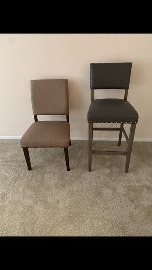 Two chairs in great condition. One brown low and another high black for Sale in Santa Ana, CA