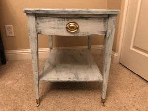 """END TABLE OR NIGHT STAND PAINTED WHITE WITH BLUE UNDERTONES AND GOLD PULL AND WHEELS. BRAND IS """"BARTON TABLES"""" MEASUREMENTS HT: 22 1/2 L: 27 1/2 W: for Sale in Fresno, CA"""