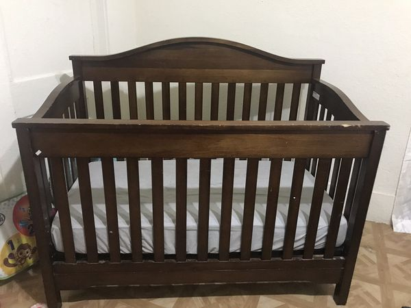 Brown crib with mattress and changing table
