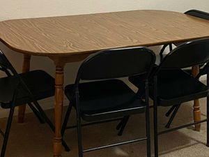 A wooden table and 4 floding metal chairs for Sale in Scottsdale, AZ
