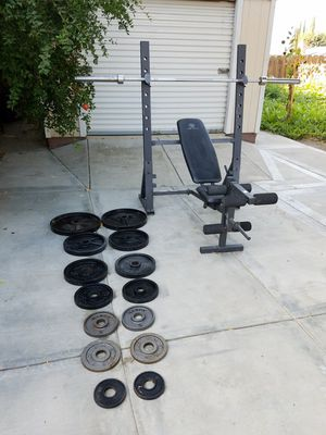 Set of olympic weights...7 ft 45 lbs olympic bar ....Golds gym bench press for Sale in Tracy, CA