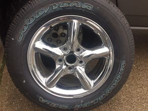 New, never mounted Goodyear Wrangler SRA P235 65 R17 mounted on a new 2002-2004 Jeep Grand Cherokee chrome rim Part#52080260AA for Sale in Medina, OH