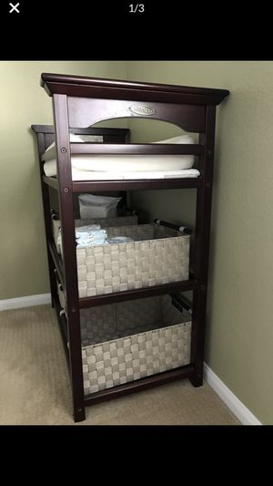 Graco cherry wood changing table bed has two separate storage sections below. Comes with cushion. INCLUDING THE BASKETS!!!!!In great condition. for Sale in Temecula, CA