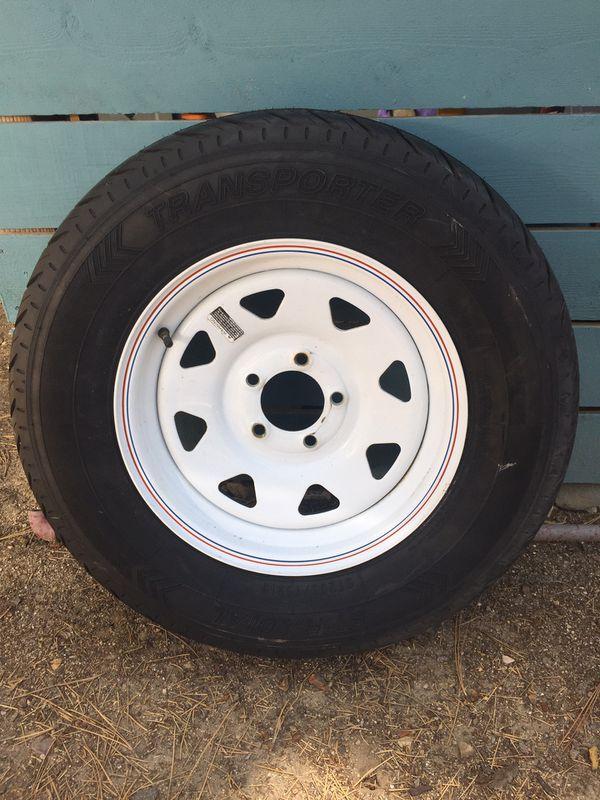 1 - trailer tire. 1 - Transporter St Radial St 205/75R15 Steel belted radial 5 lug wheel.