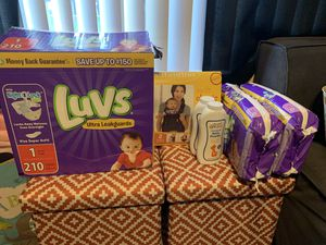 Baby newborn and size 1 diaper bundle w/ baby carrier for Sale in Gilbert, AZ