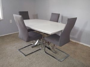 White Dinning set with New Chair Covers. Table and one of the chairs have small scuff as seen in pictures. New Gray Chair Covers for Sale in Tampa, FL
