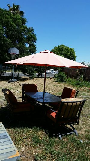 a glass table with 4 metal chairs and an umbrella for Sale in Stockton, CA