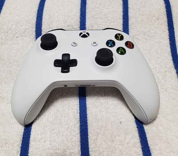white Xbox One console with controller and game