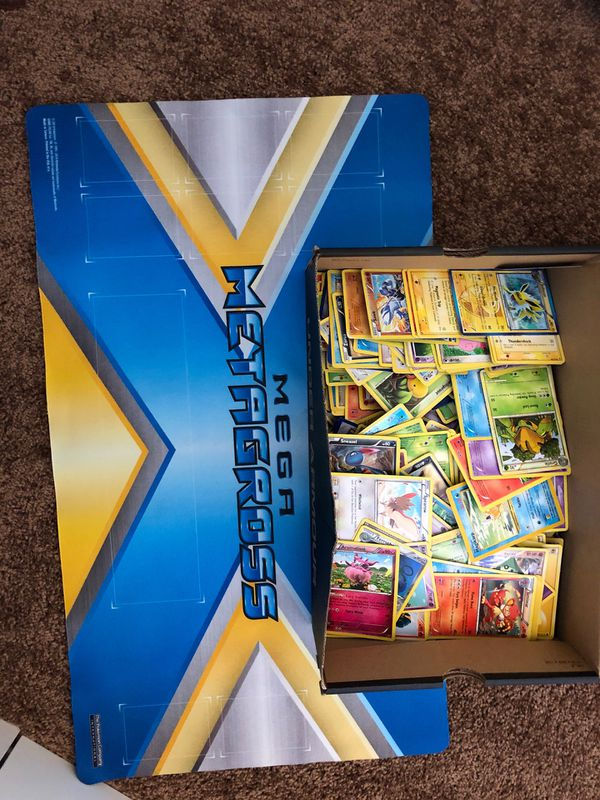 Box of Pokémon cards and Pokémon playing mat.