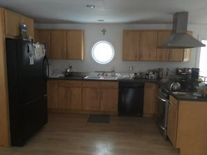 Custom made wooden cabinets stained appliances refrigerator microwave stove oven stainless steel vent over the stove countertops breakfast bar for wo for Sale in Plainville, MA
