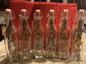 RAE DUNN GLASS BOTTLES WITH WINTER LOGOS. Added inside is a Christmas Ornament. Complete set of 6! SEE PHOTOS AMAZING CHRISTMAS DECORATION!!🎅🏽 for Sale in Naperville, IL