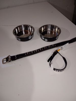 Puppy dog bowls chrome and black with paw prints both for $5.00 u can't buy one of these for that also a med size black leather spiked studded collar for Sale in Covington, KY